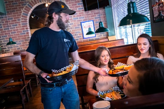 Doug Hunt, a server at Sticky Fingers Ribhouse on Main Street in Greenville, drops off food to Anna Everhart, of Gafney, Caroline Gragg, Jessica Gardner, Lindsey Rector, all of Spartanburg, Monday, May 11, 2020.