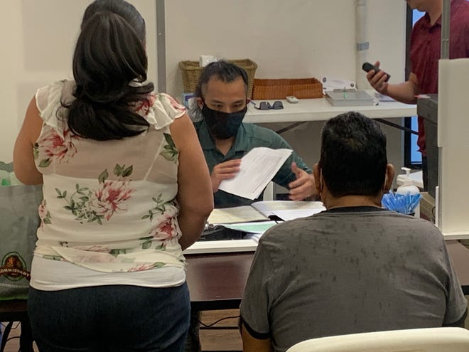 Guam Election Commission employee Albert Sanga, center, receives candidacy papers from Agana Heights Mayor Paul McDonald, right, accompanied by village administrative assistant Genedine Reyes, at the GCIC Building arcade in this file photo.