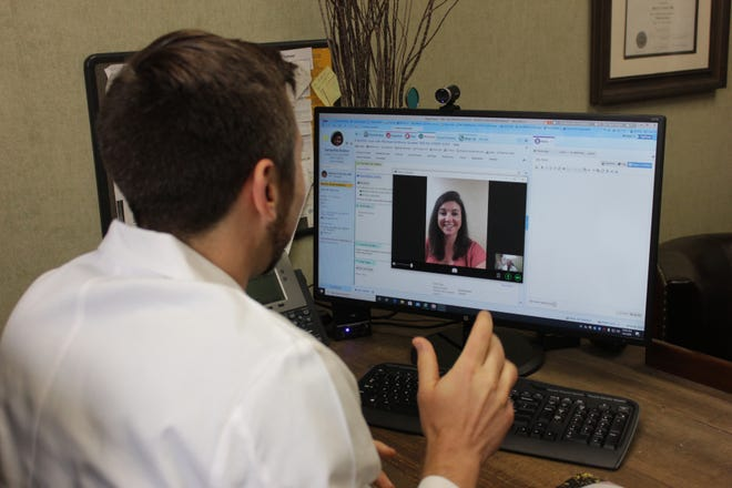 Hattiesburg Clinic Gastroenterology Dr. Michael Anthony Goebel and Samantha Andrus, practice manager at Hattiesburg Clinic, offer a look at what a telemedicine video visit looks like in this Friday, May 8, 2020, photo illustration at the clinic.