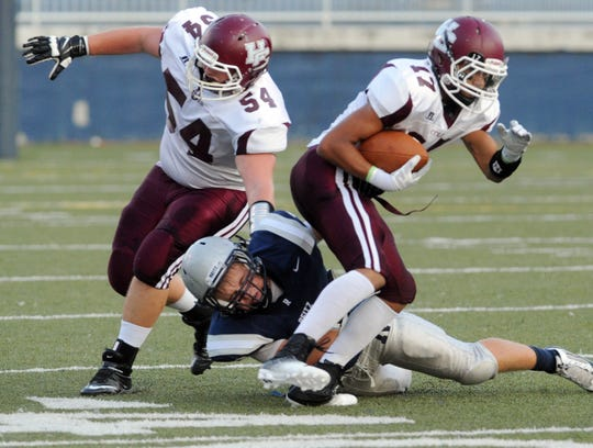 Reitz's Brandon Jones tries to tackle Henderson County's Kobe Carter,  right, during a game at the Reitz Bowl in Evansville on Friday, August 23, 2013. Henderson's Cole Roberts is at left.