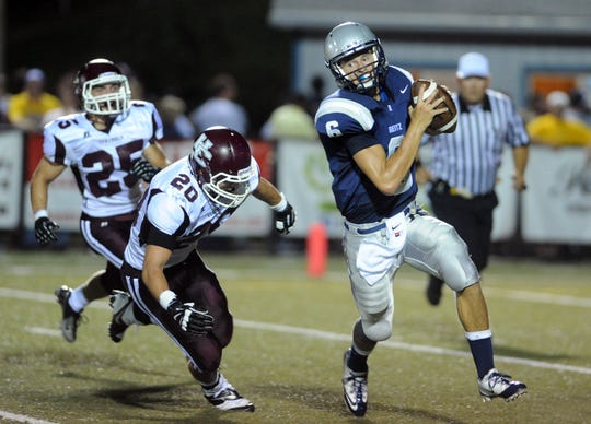 Reitz quarterback Austin Reagan runs the ball past Henderson County's Alex Greubel, left, and Russell Fuchs, far left, during the first half of a game at the Reitz Bowl in Evansville on Friday, August 23, 2013.