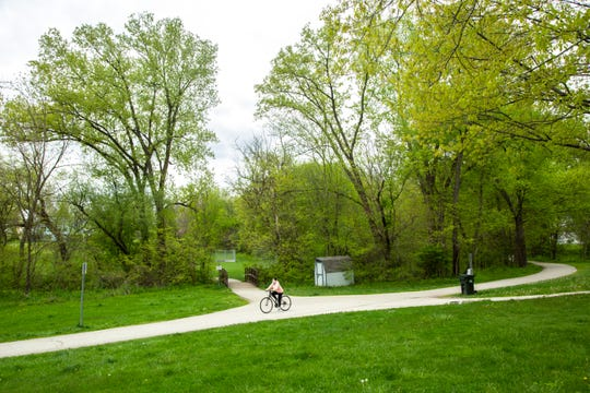 A person wearing a face mask rides a bicycle on the Willow Creek Trail during the novel coronavirus pandemic, Monday, May 11, 2020, at Willow Creek Park in Iowa City, Iowa.