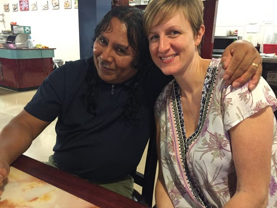 Angela Stuesse, a professor at the University of North Carolina, Chapel Hill, right, visits with Celso Mendoza in Forest, Miss., in 2016. The poultry plant worker died May 2, 2020, of COVID-19.