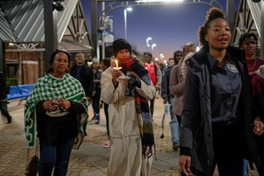 Gailya Porter (foreground), wearing a light-colored full-length coat,  joins a candlelight vigil at Jackson State University in Jackson, MIss., on Feb. 27, 2020. The event was part of several planned to commemorate the 50th anniversary of the May 15, 1970, shooting at what was then Jackson State College. Porter was among those injured. Two were killed, Phillip Lafayette Gibbs, a Jackson State prelaw major, and James Earl Green, a local high school student, during the shooting by law enforcement.