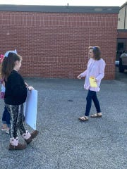 Westover Elementary teacher Elise Eads is welcomed to the school parking lot by students after completing her last chemotherapy treatment last week.