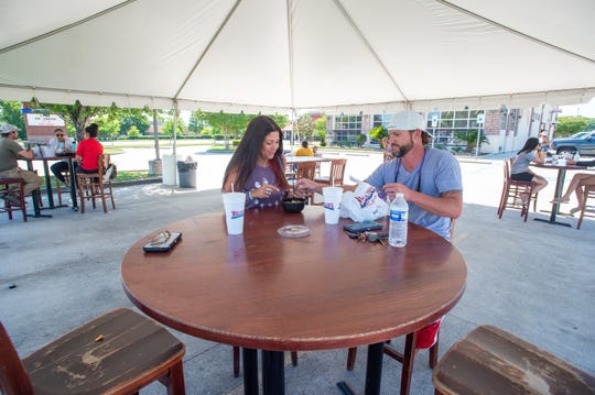 Lisa Camagere and Jarred Waguespack sit outside Walk Ons restaurant last week as Louisianans get out more and the state begins reopening.