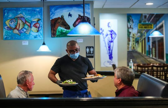 Eved Carrasco serves up lunch to two customers at Habana Blues Tapas Restaurant in downtown New Albany.