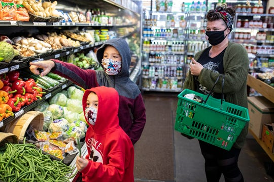 Ollie Huff, 5, from left, and brother Owen Huff, 9, shop with their mother Sarah Huff at Paul's Fruit Market on Taylorsville Road on Monday.