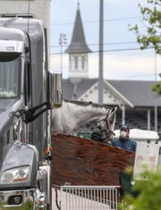 A horse is unloaded from a trailer on the backside at Churchill Downs on Monday.