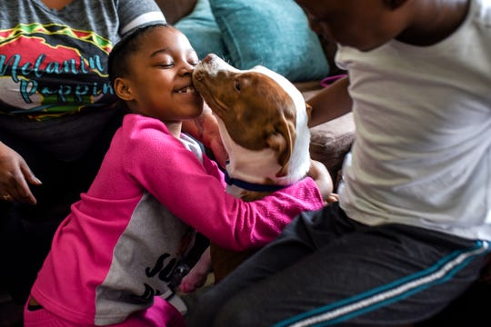 6-year-old twins A'Naijah, left, and A'Nailah Clark play with their dog Polo in their living room on Monday, May 11, 2020, at their home in Lansing. Their mother Angelia is navigating the challenges of working from home, and caring and homeschooling her four children.