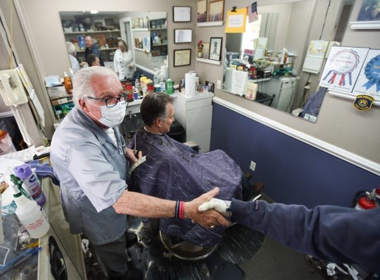 Karl Manke, owner of Karl Manke Barber Shop in Owosso, left, shakes hands with a customer while giving John Taschner of Novi a haircut, Monday, May 11, 2020. Manke has defied the governor's not to conduct business.  [MATTHEW DAE SMITH/USA Today Network]