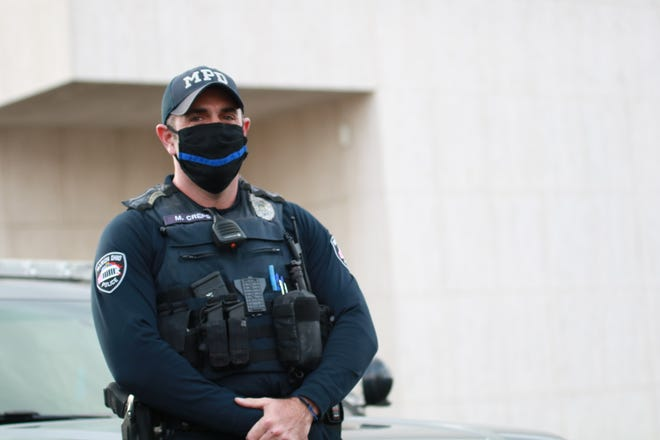 Officer Matt Creps of the Marion Police Department dons a face covering and other personal protective equipment while on patrol around the city.