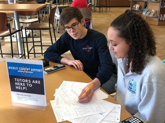 Nicolet High School junior Shayla Gwinn, right, works with a student on math homework earlier this school year when classes were in session at the Nicolet building. Gwinn has been serving as a peer tutor since September and will continue to help by doing so virtually.