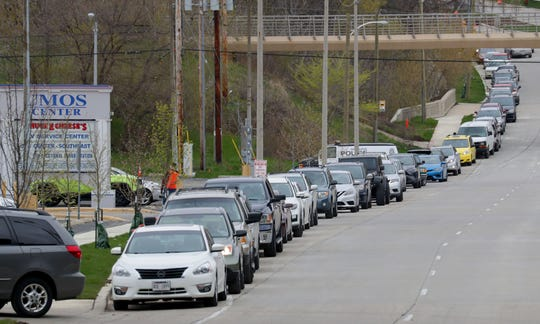 A line a people in their vehicles wait to be tested at a newly established COVID-19 testing facility at UMOS, 2701 S. Chase Ave. in Milwaukee on Monday, May 11, 2020.