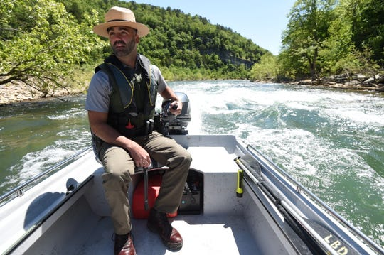 Adam Bass, a law enforcement ranger for the National Park Service patrols the Buffalo National River Saturday. During Bass' Saturday patrol of some seven miles of river, he did not encounter anyone in the closed park either on the river or the shore. The park is set to open for day use beginning Friday.