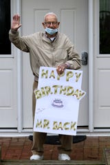 Cliff Back is shown as he waves to friends who honked their horns in Boonton for his birthday.  Back, who recently overcame coronavirus, turned 92 on Monday.  Back was a high school coach and official for more than four decades. Here he holds a sign that was given to him by one of the people in the parade.  Monday, May 11, 2020
