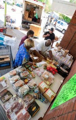 """Curtis """"Chap"""" Browder helps set up a food giveaway at his thrift store in Montgomery, Ala., on Monday May 11, 2020."""