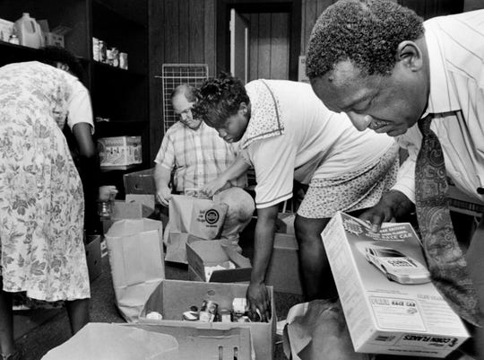"""Curtis """"Chap"""" Browder, right, along with Randy Poole, left, and Corvetta McCoy pack food items to be given out to 500 families on August 23, 1991."""