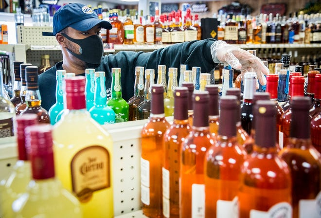 Employee Ashton Hutchings straightens up shelves at Friendly Package Liquors Monday, May 11, 2020.
