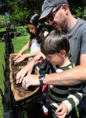 John Kaehler plants seedlings with his grandchildren Olivia Hope Black, 8 and Connor Jeffrey, 4, on Monday, May 11, 2020. Kaehler and his wife Mary Ann deLeon have been doing home improvement projects including redoing their front porch steps and planting flowers and vegetables in their Smyrna backyard with their grandchildren.