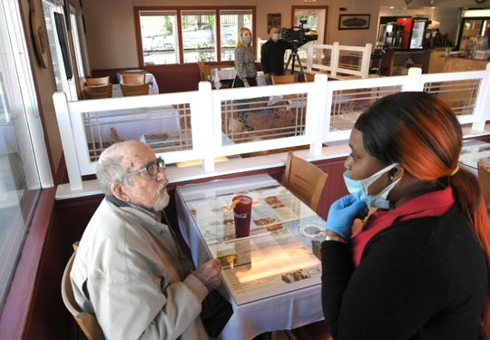 Longtime customer Chuck Carter orders breakfast from server Monique Thomas Monday, May 11, 2020, at Athens Family Restaurant in Nashville, Tenn. Carter was the first customer at the restaurant on re-opening day. Nonessential businesses have been closed for seven weeks due to the coronavirus pandemic, including no in-person dining at restaurants. Mayor John Cooper is allowing them to open in the first phase of lifting coronavirus restrictions.