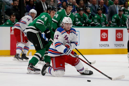 New York Rangers right wing Julien Gauthier (12) reaches for the puck in front of Dallas Stars left wing Roope Hintz (24) during the first period of an NHL hockey game in Dallas,.