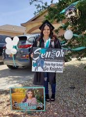 Brianna Sanchez, a senior at Oñate High School, stands in front of her home with signs distributed by Las Cruces Public Schools.