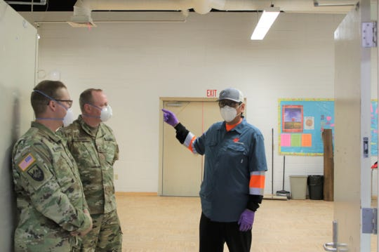 Navajo Nation President Jonathan Nez, center, talks with U.S. Army Corps of Engineers personnel on April 29, 2020 during a tour of the alternate care site the Corps built inside Northwest High School in Shiprock.