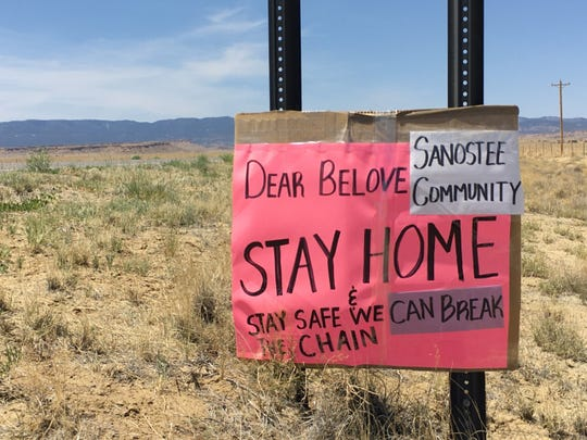 Signs that encourage the public to stay at home have appeared in communities on the Navajo Nation. This sign is pictured on May 8 on Navajo Route 34 in Sanostee.