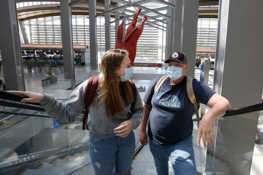 Southwest Airline passengers Anna Bell, left, and her father, Steve, wear face masks as they go to the boarding gates at Sacramento International Airport in Sacramento, Calif., Monday, May 11, 2020. Beginning Monday Southwest and several other airlines are requiring passengers to wear face coverings or masks during flights. (AP Photo/Rich Pedroncelli)