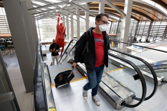 Southwest Airline passenger Robert Civettini wears a face mask as he goes to the boarding gate at Sacramento International Airport in Sacramento, Calif., Monday, May 11, 2020. Beginning Monday Southwest and several other airlines are requiring passengers to wear face coverings or masks during flights. (AP Photo/Rich Pedroncelli)