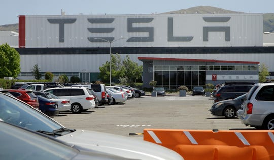 Vehicles are seen parked at the Tesla plant Monday, May 11, 2020, in Fremont, Calif. The parking lot was nearly full at Tesla's California electric car factory Monday, an indication that the company could be resuming production in defiance of an order from county health authorities. (AP Photo/Ben Margot)