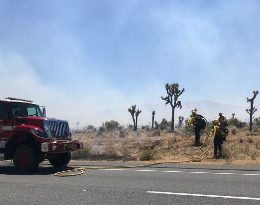 San Bernardino County firefighters battle a brush fire off Highway 62, between Yucca Valley and Joshua Tree, Monday, May 11, 2020.