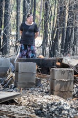 Leslie Perryman looks over the remains of her stepson Brian Perryman's home in Milton on Monday, May 11, 2020.  All of the Perryman family's belongings were destroyed when their rental house was consumed by the Five Mile Swap Fire last week.