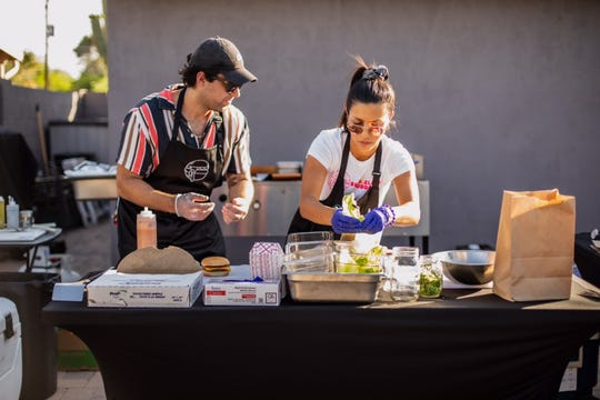 Connor Dubin and Izzy Salazar make cheeseburgers at their vegan pop-up, Shameless Burger, on May 8, 2020.