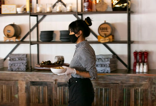 Cristina Dorado, a server at the Macintosh, serves food as the Phoenix restaurant reopens for the first time for dine-in service since mid-March, on May 11, 2020. Restaurants across the state were permitted to reopen for dine-in service on Monday following certain guidelines.