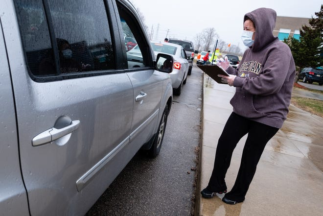 Marysville Public Schools Director of Food Service Pamela Heintz wears a face mask as she talks to someone through a car window Tuesday, April 7, 2020, at Marysville High School.