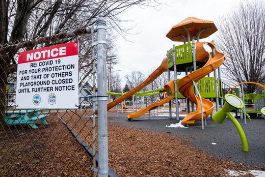 A sign telling visitors that the playground is closed hangs on the fence at Optimist Park Tuesday, March 24, 2020, in Port Huron. Park playgrounds were being reopened as of Tuesday, June 2.