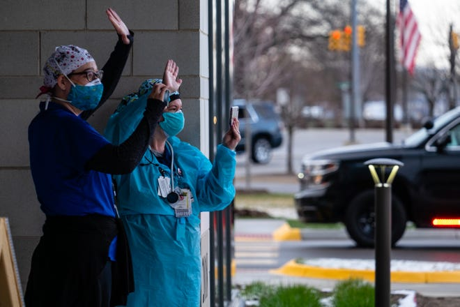 Two McLaren Port Huron employees wave as first responders parade past them Wednesday, April 15, 2020.