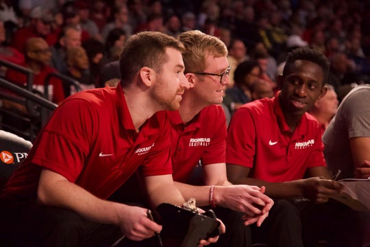 Former New Oxford High boys' basketball coach Sean Bair, center, sits on the bench during a University of Arkansas men's basketball game. Bair served as a graduate assistant for the Razorbacks last season.