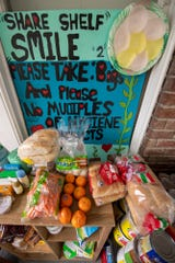 A sign decorated with hearts announces the 'Share Shelf' food pantry on Ashley Martin's porch.
