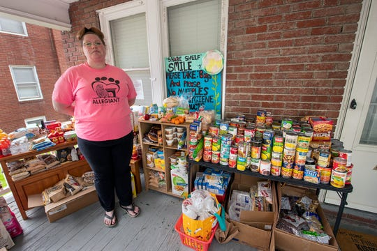 Ashley Martin with her re-stocked 'Share Shelf' food pantry on the porch of her home in the 500 block of Atlantic Avenue. Everything was taken recently overnight while it was under a tarp. She has since restocked with the help of donations.