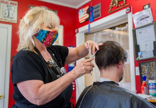 Sheri Van Ness, owner of Salon Van Ness, cuts David Chism's hair on the first day hair salons were allowed to reopen.