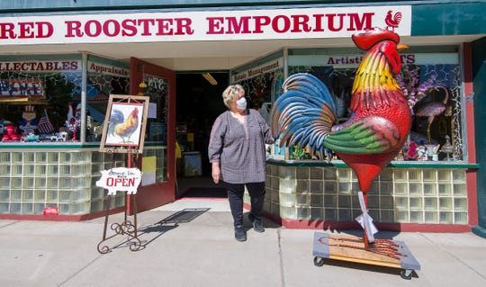 Jane Montalbano, sole proprietor of Red Rooster Emporium, wheels out her signature 5' tall metal rooster in front of her business for the first time since being closed for more than a month.
