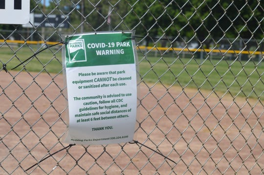 COVID-19 warning sign is strung to a fence at a baseball field at East Redding Little League on Friday, May 8, 2020.
