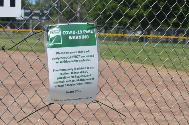 A COVID-19 warning sign is attached to a fence at a baseball field used by East Redding Little League on Friday, May 8, 2020.