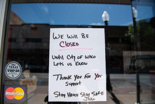A hand-written signs alerts customers that Jake's Texas Tea House in Waco is closed indefinitely.