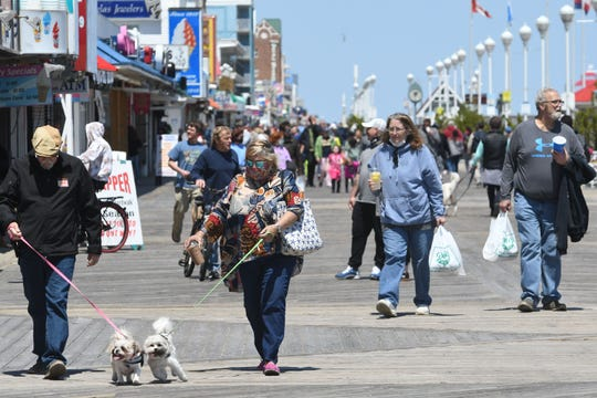 Folks stroll the Boardwalk and beach in Ocean City Sunday, May 10, 2020 after the town  opened the beach and Boardwalk that had been closed since mid-March due to  the COVID-19 pandemic.