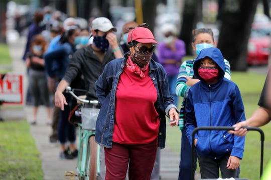 People line up for food at a food distribution point for people economically impacted by the coronavirus pandemic, organized by New Orleans City Councilman Jay Banks, in New Orleans, Wednesday, April 29, 2020. (AP Photo/Gerald Herbert)