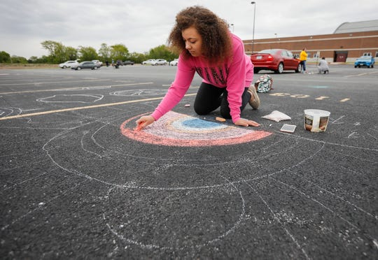 Adora Snead, a senior at Willard High School, decorates her parking space at the school with chalk on Monday, May 11, 2020.
